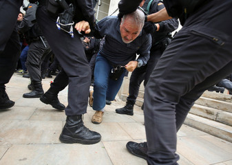 Man is dragged away by officers outside polling station for Catalonia referendum in Sant Julia de Ramis