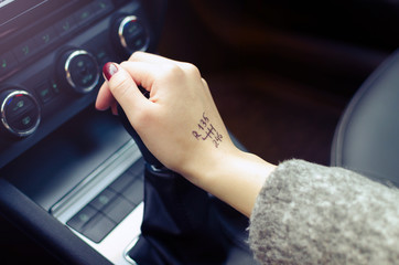 woman switching manual transmission with the scheme on the hand