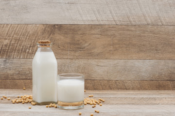 Bottle of soy milk and soybean on wooden table