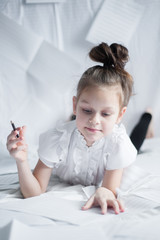 A little girl lies on her belly among blank sheets of paper and holds a pencil in her hand