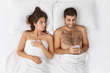 Young brunette female being annoyed with husband who is obsessed on playing online games at smart phone, wants more care and love. Suspicious woman feels jealosy as boyfriend messages on mobile
