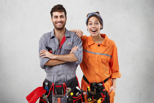 Happy excited female and male plumber wear uniform with tool belts, being glad to repair bathtub, recieve pleasant comments from clients, isolated over white concrete wall. Success, repairing concept