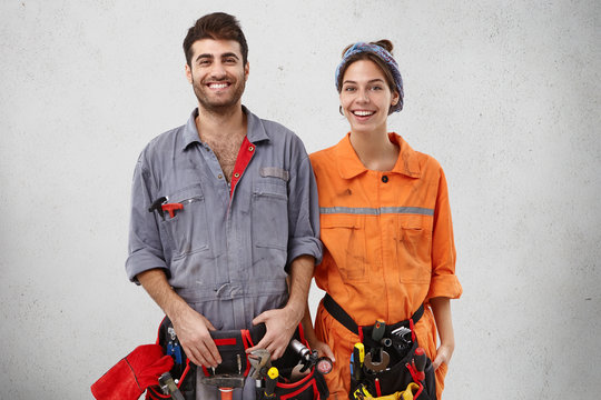 Glad bearded handyman and his female companion stand next to each other, feel support and help, work as friendly team, remodell objects, smiling gladfully, isolated over white concrete studio wall