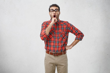 Picture of emotional adult Caucasian brunette guy with stubble wearing old fashioned spectacles and plaid shirt holding hand on chin, having shocked look as some bright mind crossed his mind