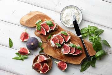 Fresh figs, basil leaves and philadelphia cream cheese bruschetta on white wooden table, top view