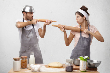 Serious cook competitors pretend that rolling pin is gun, look at each other as on shooting mark, try to prove rightness or case, stand at kitchen table with ingredients and hand made pastry