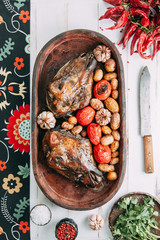 the bull's head baked with vegetables and potatoes and garlic on a wooden Board