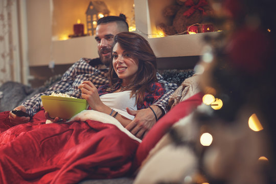 Man and woman in bed watching tv and eating pop corn