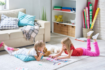 Portrait of cute little sisters coloring pictures together lying on floor on thick plush carpet in cozy living room at home