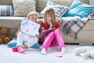 Portrait of two cute little girls playing together sitting on thick carpet at home, using digital tablet and coloring pictures