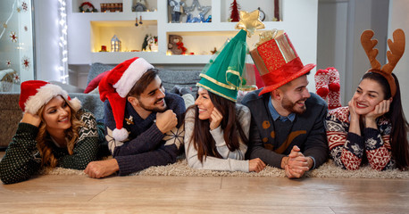 Friends with Christmas hats enjoying together