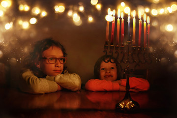 Low key image of jewish holiday Hanukkah background with two cute kids looking at menorah (traditional candelabra) and burning candles