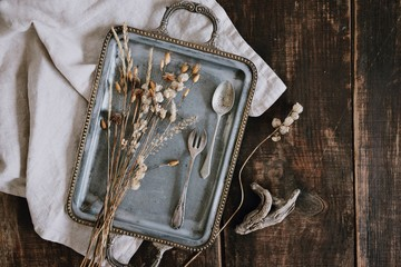 Still life with elegant fancy vintage tray with silver cutlery, dried beautiful and tiny field flowers and linen light grey napkin on brown old wooden dark table background. Top view.