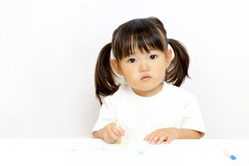 クレヨンで絵を描いて遊ぶ幼い女の子のカメラ目線