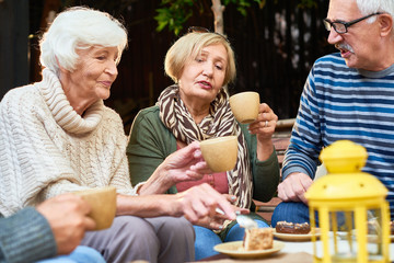 Elderly people wearing warm clothes enjoying each others company while having tea party with delicious cake outdoors