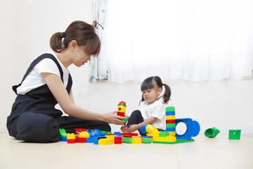 お母さんと玩具で遊ぶ幼い女の子