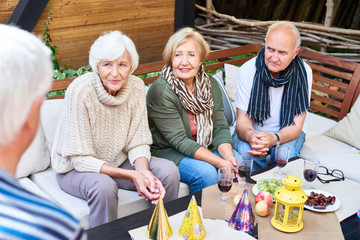 Senior friends wearing warm clothes having good time together while gathered together at lovely outdoor cafe, they listening to unrecognizable elderly man with interest