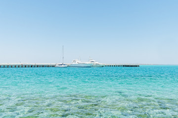 Three large white boats moored in the Red Sea under a blue sky.
