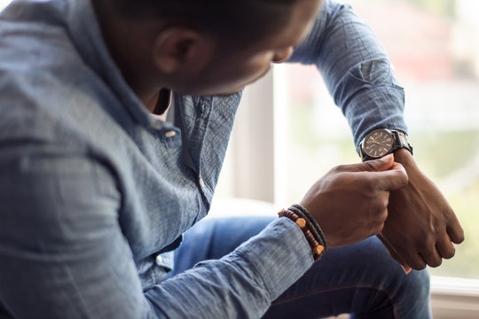 Handsome african man looking at his watch while sitting in his home or office