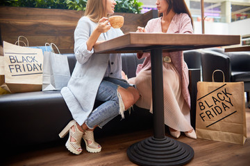 Low section portrait of two beautiful young women in shopping mall chatting and  drinking coffee at cafe table surrounded by paper bags with purchases