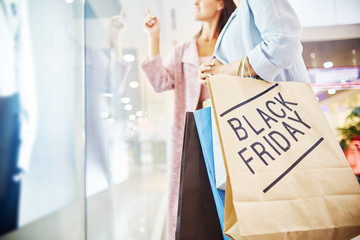 Mid section portrait of two happy young women shopping in mall, looking at window display and smiling, holding paper bags with BLACK FRIDAY written on it