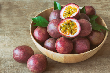 Passion fruit on wood bowl put on wood table in vintage tone style for background or wallpaper. Ripe passion fruit so sweet and sour suitable make dessert for summer. Passion fruit is tropical fruit.