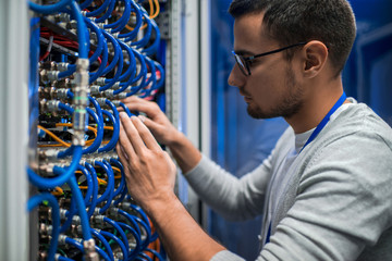 Side view portrait of young man connecting wires in server cabinet while working with supercomputer in data center
