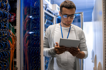 Portrait of modern young man using digital tablet standing by server cabinet while working with supercomputer in blue light