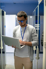 Portrait of young man using laptop standing by server cabinets in data research center