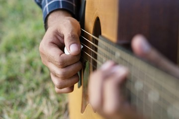 Acoustic guitar guitarist playing. Musical instrument with performer hands in parks.