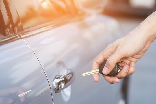 Cropped view of  Closeup of a man's hand inserting key into the door lock of a car