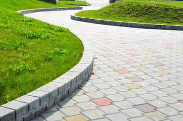Curved Garden Stone Path Pesperctive View. Multicolored Sidewalk Tile Road Background