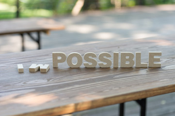 The letters word IMPOSSIBLE in motivation meaning of impossible make it possible concept. On wood background.