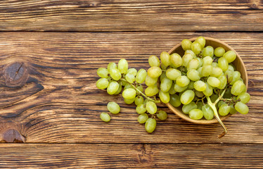Bowl with fresh ripe green grapes on wooden background. Top view.