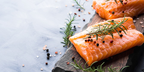 Photo sur Plexiglas Poisson Raw salmon pieces on wooden board with herbs, salt and spices