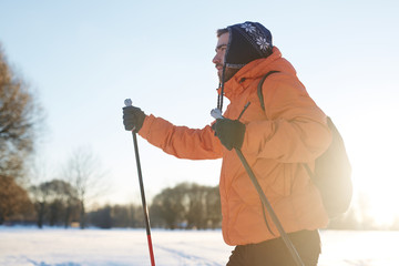Active backpacker skiing in rural environment on winter weekend