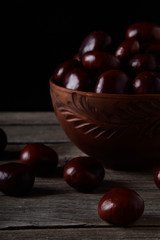 Fresh chestnuts in a bowl on an old wooden table. Group of chestnuts. Chestnuts - fruits horse chestnut - Aesculus hippocastanum. Dark background. Autumn background