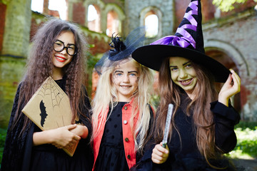 Group of little witches in halloween costumes enjoying outdoor party