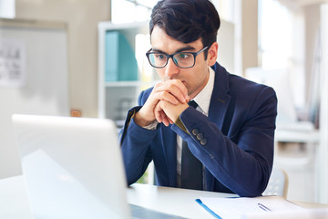 Businessman concentrating on reading online data by workplace