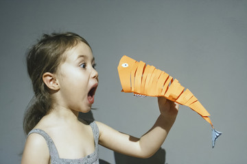 Baby emotions: the child screams, is angry with the paper fish