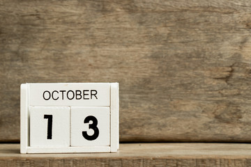 White block calendar present date 13 and month October on wood background