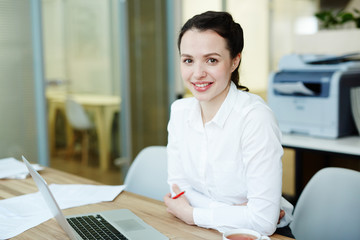 Attractive businesswoman in white shirt sitting by workplace in front of laptop
