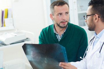 Highly professional young doctor explaining X-ray results to worried patient and trying to calm him down during appointment at office