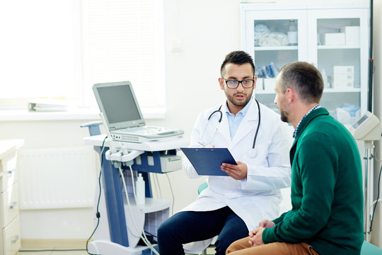Middle-aged bearded patient having consultation with highly professional physician at modern office, they discussing diagnosis and possible treatment