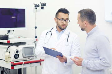 Handsome young doctor in eyeglasses discussing medical test results with male patient and prescribing necessary treatment, interior of modern office on background