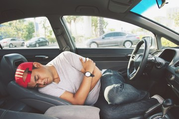Tired young man driving his car. sleeping inside his car, exhausted.