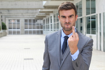 Moody businessman showing a middle finger
