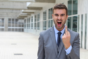 Moody businessman screaming and showing the middle finger