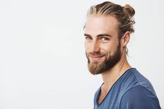 Close up portrait of handsome manly guy with beard posing in three quarters, looking in camera and happily smiling. Lifestyle concept.