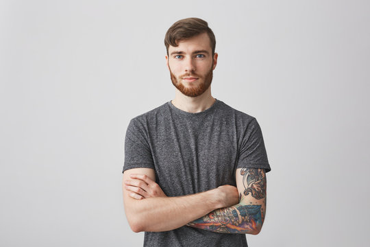 Portrait of beautiful young man with ginger beard and tattooed hand looking in camera with gentle smile and calm expression.